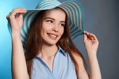 Beautiful happy teenager girl in hat. Beauty smiling young woman over blue background.healthy teeth Stock Photo