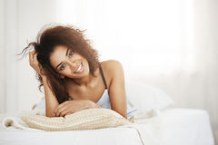 Beautiful happy tender african girl lying on pillow at home smiling looking at camera woke up on sunny day in the Stock Photography