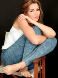 Beautiful Happy Thoughtful Carefree Young Woman Sitting in a Chair Royalty Free Stock Image