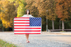 Beautiful happy woman with American flag celebrating independence day Royalty Free Stock Photo