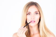 Beautiful happy woman applying shine on lips Royalty Free Stock Photography