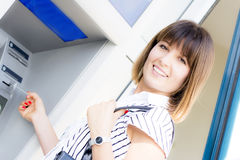 Beautiful happy woman at the atm Royalty Free Stock Images