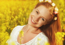Beautiful happy woman in awreath in meadow with yellow flowers Royalty Free Stock Photos