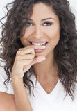 Beautiful Happy Woman Biting Her Finger. Studio portrait of a beautiful young mixed race Latina Hispanic woman smiling and biting her finger with perfect teeth royalty free stock image