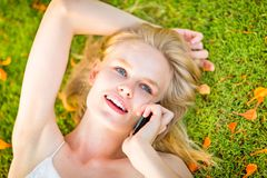 Beautiful happy woman calling on a cellphone while lying on the green grass during autumn time. royalty free stock photos