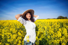 Beautiful happy woman in canola field in sunny day Royalty Free Stock Photography