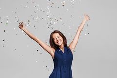 Beautiful happy woman at celebration party with confetti falling everywhere on her. Birthday or New Year eve celebrating concept stock photos