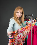 Beautiful happy woman in the clothes store. Beautiful woman lookong the dress Stock Photos