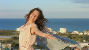 Beautiful happy woman dancing with scarf, amazing sea landscape in background stock footage