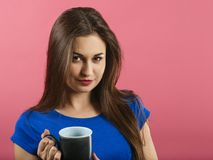 Beautiful happy woman drinking coffee. Photo of a gorgeous young woman drinking coffee over a pink background Stock Image