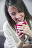 Beautiful happy woman drinking cup of coffee sitting home by the  Christmas tree. Royalty Free Stock Photography