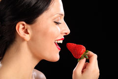 Beautiful happy woman eating red strawberry fruit Royalty Free Stock Photo