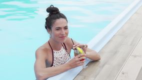 Beautiful happy woman enjoying cocktail at the swimming pool stock video footage