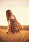 Beautiful happy woman in field at sunset Stock Photo