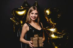 Beautiful happy woman with gift box at celebration party. Birthday or New Year eve celebrating concept. stock photography