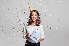 Beautiful happy woman with gift box at celebration party with confetti falling everywhere on her. royalty free stock image