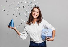 Beautiful happy woman with gift box at celebration party with confetti falling everywhere on her. royalty free stock images