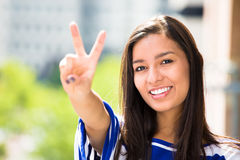 Beautiful happy woman giving a victory sign relaxing on a summer day on a balcony Royalty Free Stock Image