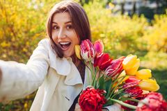 Beautiful happy woman holding bouquet of tulups and taking selfie. Girl having fun stock images