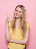 Beautiful happy woman holding water in plastic bottle and ready to drink Royalty Free Stock Images