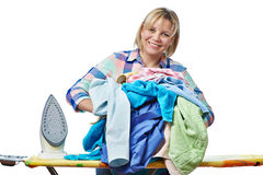 Beautiful happy woman housewife holding pile of laundry for iron Royalty Free Stock Photography