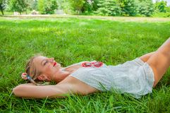 Beautiful happy woman lies on the grass in summer royalty free stock photos