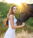Beautiful happy woman with long hair next horse Stock Photos