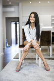 Beautiful happy woman with long legs in a nice white room Stock Photography