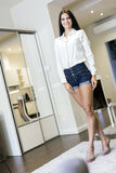 Beautiful happy woman with long legs in a nice white room Stock Images