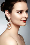 Beautiful happy woman in luxury fashion earrings. Diamond shiny jewelry with brilliants. Sexy retro style portrait Royalty Free Stock Photo
