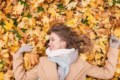 Beautiful happy woman lying on autumn leaves Royalty Free Stock Photography