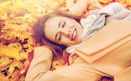 Beautiful happy woman lying on autumn leaves Stock Photo