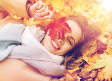 Beautiful happy woman lying on autumn leaves Royalty Free Stock Photos