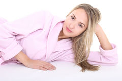 Beautiful happy woman lying in bathrobe Stock Image