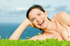 Beautiful happy woman lying in grass Stock Photos