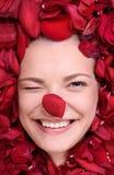 Beautiful happy woman lying in petal roses Stock Photography