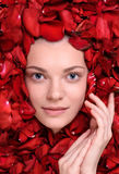 Beautiful happy woman lying in petal of roses Royalty Free Stock Photography