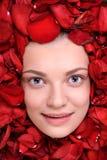 Beautiful happy woman lying in petal of roses Royalty Free Stock Image