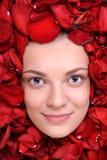 Beautiful happy woman lying in petal of roses Stock Images