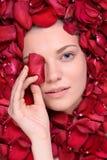 Beautiful happy woman lying in petal of roses Royalty Free Stock Photos