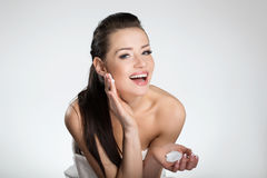 Beautiful happy woman moistening face with cream Royalty Free Stock Images
