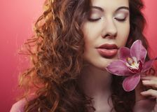 Beautiful happy woman with orchid flower over pink background Royalty Free Stock Image