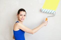 Beautiful, happy woman paints wall Stock Photo