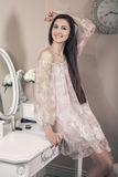 Beautiful happy woman with pink dress and long black hair in her room near her dressing table posing before party. Royalty Free Stock Image