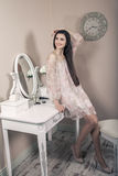 Beautiful happy woman with pink dress and long black hair in her room near her dressing table posing before party. Stock Photo