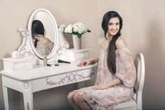 Beautiful happy woman with pink dress and long black hair in her room near her dressing table posing before party. Royalty Free Stock Photography