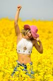 Beautiful happy woman on rape field Royalty Free Stock Images
