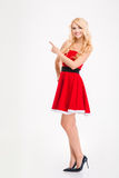 Beautiful happy woman in red santa claus costume pointing away Stock Photos