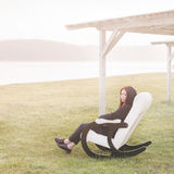 Beautiful happy woman relax in chair on lake morning Stock Photography