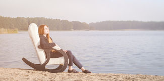 Beautiful happy woman relax in chair on lake morning Royalty Free Stock Photography